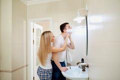 Couples pendant le matin dans la salle de bains faisant l'hygiène personnelle Photos stock