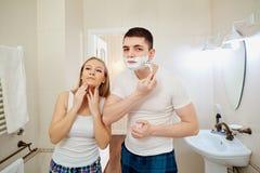 Couples pendant le matin dans la salle de bains faisant l'hygiène personnelle Images stock