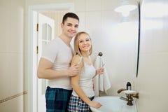 Couples pendant le matin dans la salle de bains faisant l'hygiène personnelle Photos libres de droits