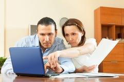 Couples pensifs calculant quelque chose à la maison intérieur Photographie stock
