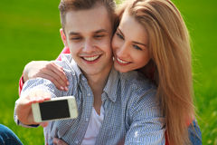 Couples with phone taking  self portrait at the park Royalty Free Stock Photography