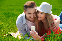 Couples with phone taking selfie self portrait at the park Stock Photography