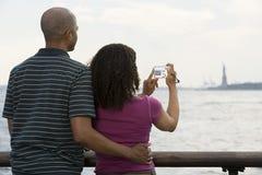 Couples photographiant la statue de la liberté Image libre de droits