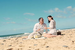 Couples picnicking on the beach Stock Photo