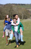 Couples piggybacking in field Royalty Free Stock Image