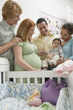 Couples Playing With Baby. Two happy multiethnic couples playing with baby by cradle Royalty Free Stock Photo