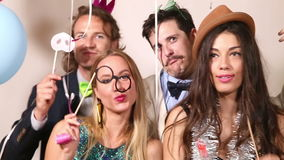 Couples playing with funny props in party photo booth. Two beautiful couples playing with funny props in party photo booth stock video