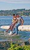 Couples plus anciens heureux éclaboussant des pieds dans l'eau Photographie stock