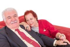 Couples pluss âgé élégants se reposant sur un sofa rouge Image stock