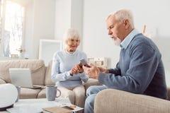 Couples pluss âgé agréables étant collés à leurs téléphones Images stock