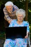 Couples pluss âgé ayant l'amusement avec l'ordinateur portable dehors photos stock
