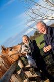 Couples pluss âgé choyant un cheval dans un pré photographie stock