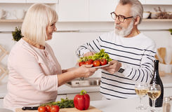 Couples pluss âgé de sourire préparant le dîner de famille ensemble dans la cuisine Photographie stock