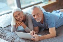 Couples pluss âgé de sourire se situant dans le lit tout en se reposant Photographie stock