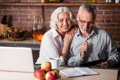 Couples pluss âgé faisant des notes dans une cuisine Images stock