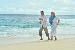 Couples pluss âgé fonctionnant sur la plage Images libres de droits