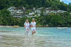 Couples pluss âgé fonctionnant sur la plage Photo libre de droits