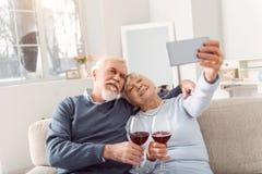 Couples pluss âgé gais prenant le selfie tout en buvant du vin Image stock