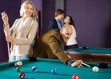 Couples pluss âgé jouant la piscine Image libre de droits