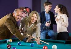 Couples pluss âgé jouant un jeu des billards jeune drinkin de couples Images libres de droits