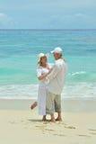 Couples pluss âgé marchant le long du bord de la mer Photos stock