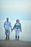Couples pluss âgé marchant le long du bord de la mer Image stock