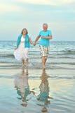 Couples pluss âgé marchant le long du bord de la mer Image libre de droits