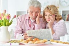 Couples pluss âgé prenant le petit déjeuner et lisant un journal Image stock