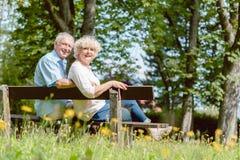 Couples pluss âgé romantiques se reposant ensemble sur un banc dans un jour tranquille photo stock
