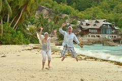 Couples pluss âgé sautant sur la plage Photo stock
