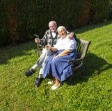 Couples pluss âgé se reposant dans leur jardin sur un banc Image stock