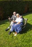 Couples pluss âgé se reposant dans leur jardin sur un banc Images stock