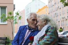 Couples pluss âgé souriant et parlant tout en se reposant sur un banc de parc Images stock