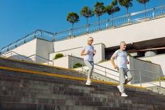 Couples pluss âgé sportifs fonctionnant en bas des escaliers Image stock
