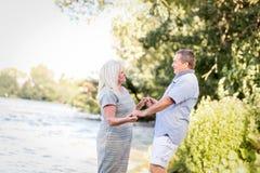 Couples pluss âgé tenant des mains par le lac Image stock