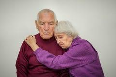Couples pluss âgé tristes sur un fond gris Images libres de droits
