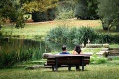 Couples posés sur le banc en parc images stock
