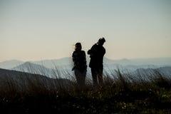 Couples posés sur une silhouette de montagne Photos stock