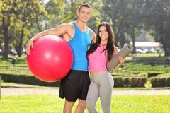 Couples posant en parc avec l'équipement de forme physique Image libre de droits