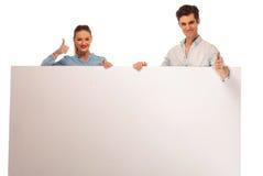 Couples posant tenant un panneau d'affichage vide Image stock