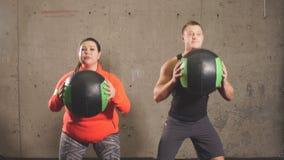 Couples positifs émotifs faisant des exercices avec des boules au centre de fitness clips vidéos