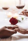 Couples positifs d'Afro-américain tenant des mains dans le café Images stock