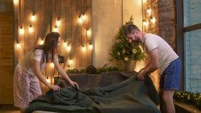 Couples positifs dans des pyjamas faisant le lit ensemble banque de vidéos