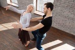 Couples positifs de danse tangoing dans la salle de bal Photo libre de droits