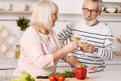 Couples positifs des retraités appréciant le champagne dans la cuisine Images libres de droits