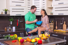 Couples positifs faisant cuire et démontrant la joie tout en se tenant dans le k Photo stock