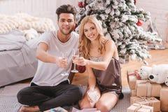 Couples positifs heureux appréciant leur célébration de Noël Photo stock
