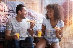 Couples positifs heureux mangeant d'une pizza Photo libre de droits