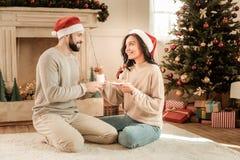 Couples positifs heureux mangeant des biscuits photos stock
