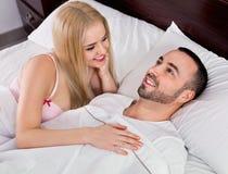 Couples positifs heureux posant dans le lit de famille Images stock